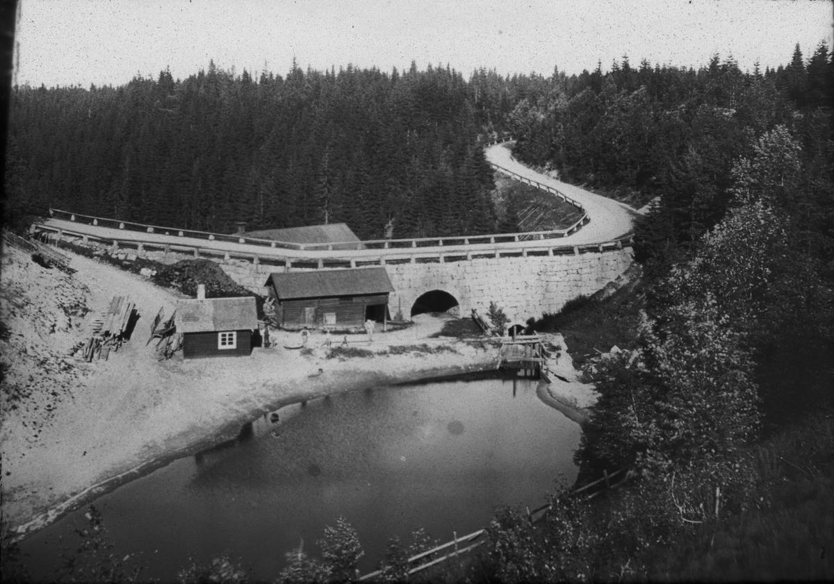 Diapositiv med motiv av väg och viadukt med litet hus framför. Bilden är tagen vid Solvarbo kvarnen, Gustafs socken, Säters kommun