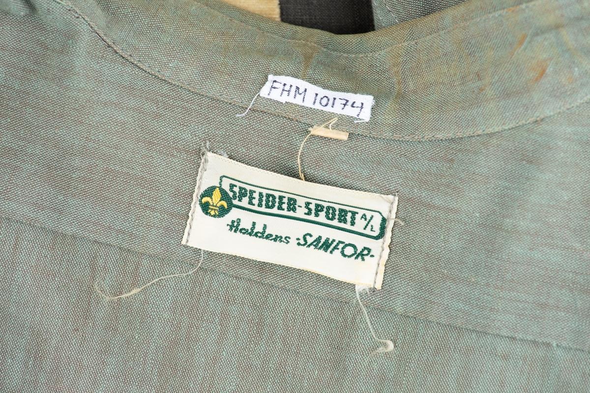 """Speiderskjorte i militærgrønn bomull. Mrk:""""Speider--sport A/S Haldens SANFOR"""" str.37. Påsydd speideremblem på venstre brystlomme. Merke på høyre brystlomme:""""1 NORDSTRAND"""".God tilstand. Fabrikkprodusert."""