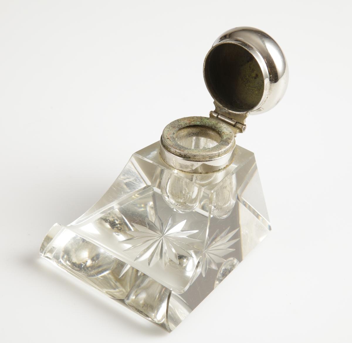"""Bläckhorn av glas, med mynning och lock i ostämplat nysilver. Glaset är gjutet och sedan """"formslipat"""" med lutande sidor och längst fram en vagga till bläckpennan. Underst en skärslipad stjärna."""