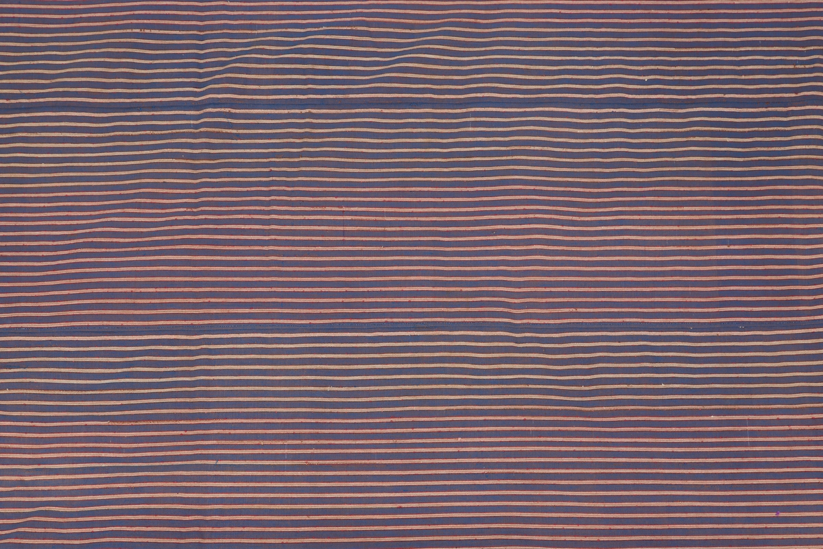 Lappeteppe. Antakelig brukt som sengeteppe 7 overbredsel. Fylt innvendig med ukkpledd og lignende til et tykt lag. Overside sydd lappeteknikk, med maskinsøm. Stoff i mange farger og kvaliteter, Lappeteknikk 6 sorte midtfelt, mangefarget mønster rundt      Undersiden er et antakelig håndvevet bomullstoff, stripet i blått og hvitt/naturfarget med røde render   Antakelig fra Gaavim i Kroer, se intern opplysning