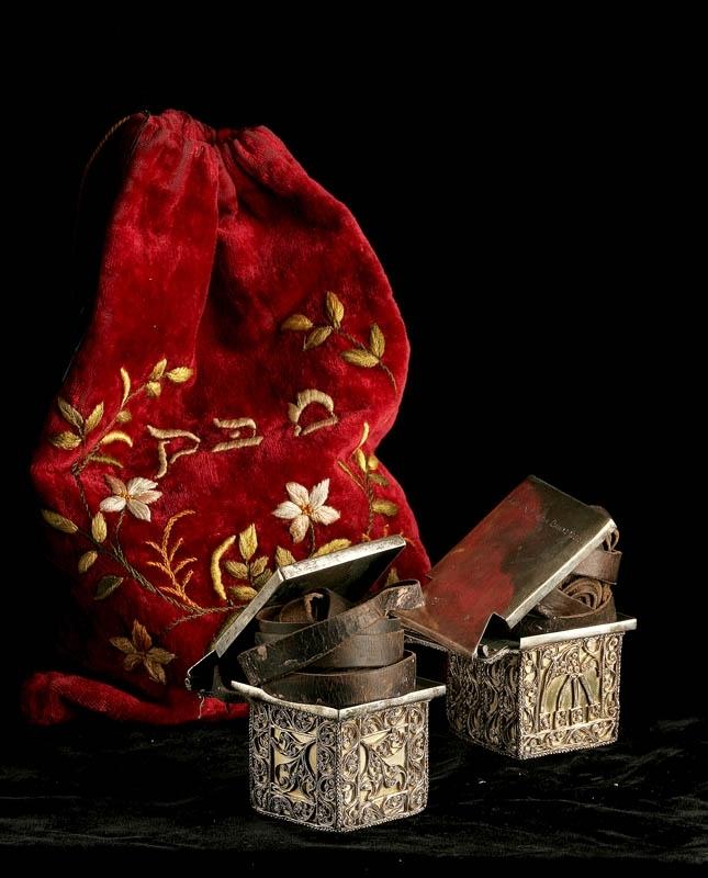 Påse av röd sammet, klädd invändigt med beige siden. Broderad dekor i form av blommor och hebreisk text på ena sidan, och en davidsstjärna och 5662 på andra sidan.