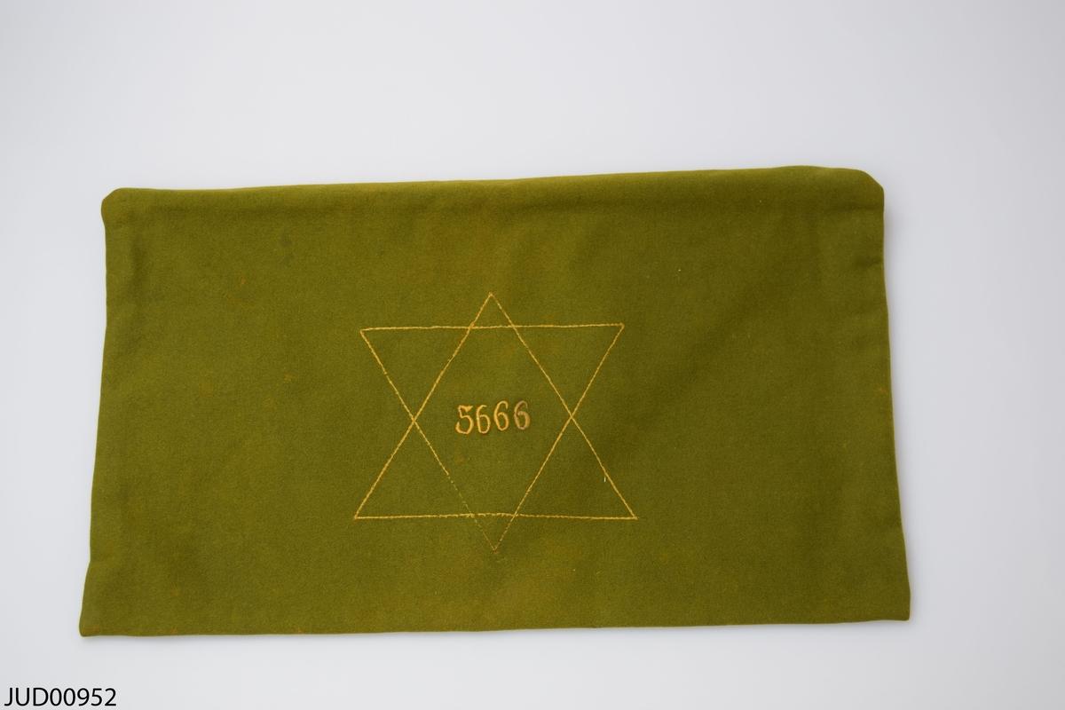 Broderad ros samt två bokstäver i gult på ena sidan. Davidsstjärna och årtalet 5666 (1905/06) på andra.
