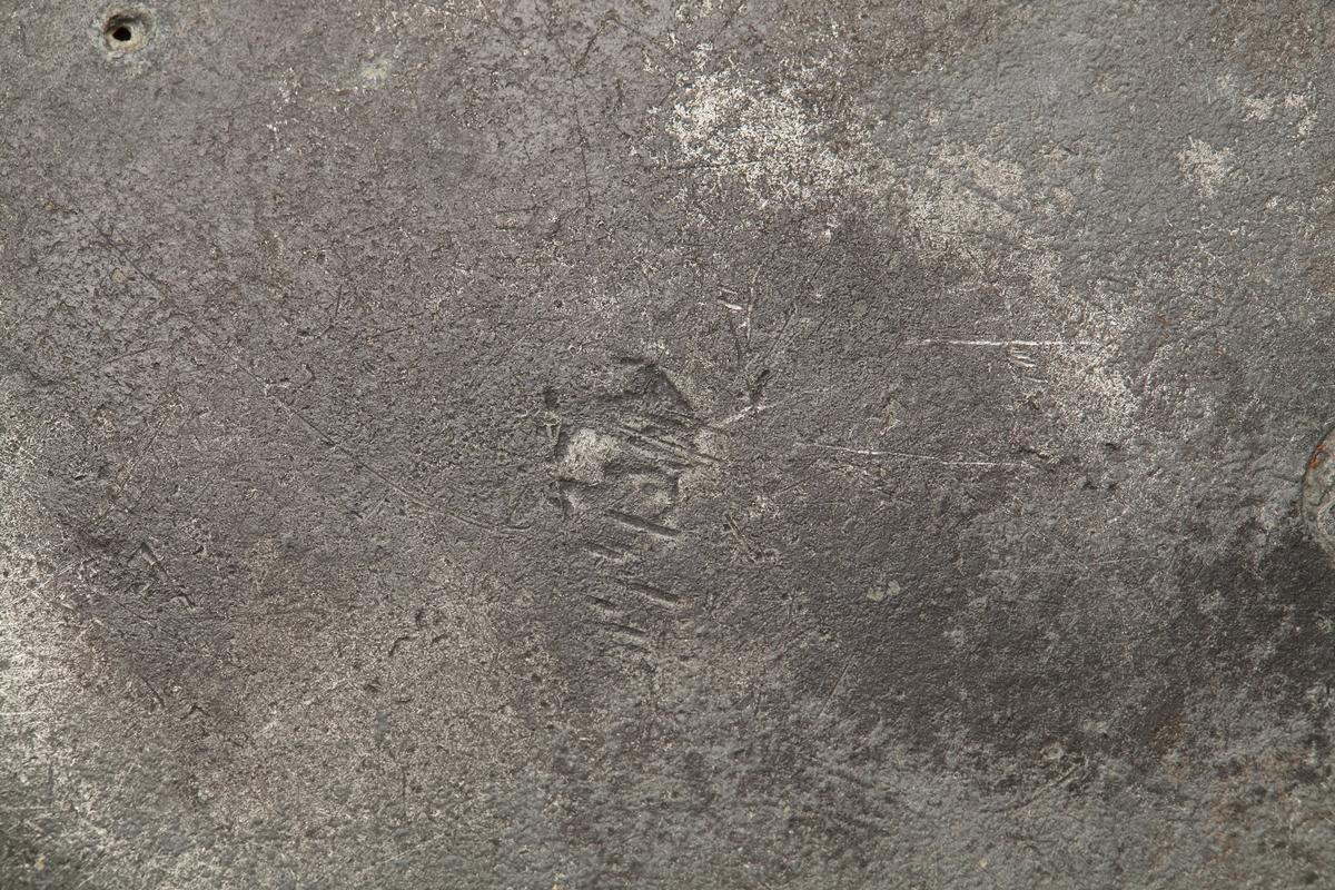 Tinntallerken. Har to stempler på baksiden. Det ene stempelet har ei krone øverst over et rundt symbol, som har to tunger øverst og tre tunger nederst. Det kan være et bymerke inni en rose, med fyrstekrone over rosen. Dette ble brukt i laugstiden fra 1685-1830. Det som er inni rosen er vanskelig å se. Det andre stempelet er mer uklart, men ser ut til å være rundt.