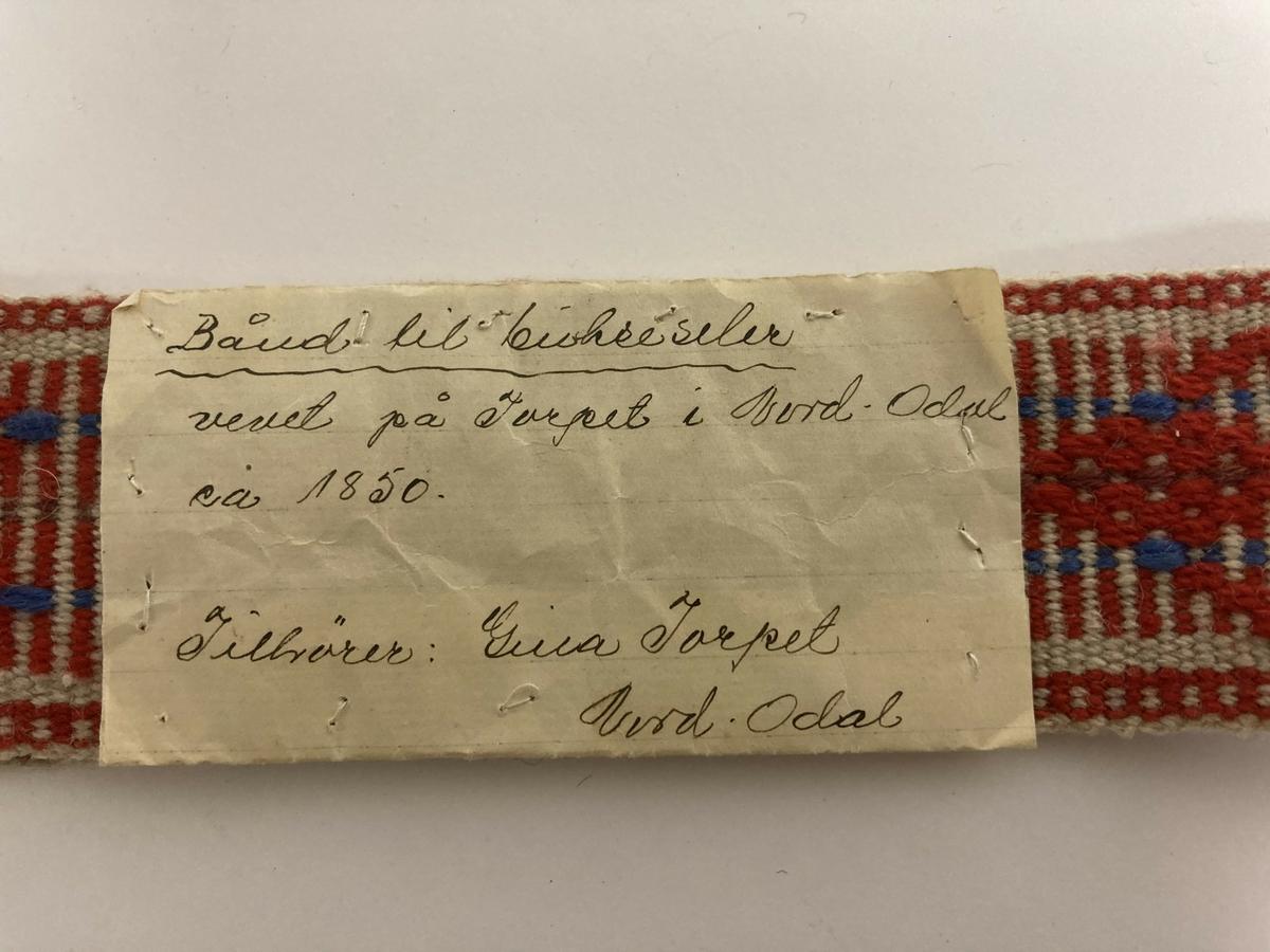 Vevde band til bukseseler, to stk, sydd sammen med lapp, skrevet av Gina Torpet (tidligere eier). Målene angir lengde og bredde på hvert enkelt band.