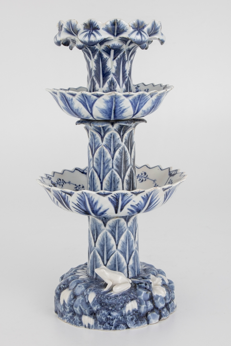 Blåhvit bordoppsats med tre etasjeskåler rundt en stamme. Stammen og utsidene av skålene er dekt med palmeblader i relieff. I toppen avsluttes stammen i en palmekrone med utoverhengende palmeblader. Palmekronen fungerer som holder til den øverste skålen som har kurvform. På innsiden av skålene musselmønster. På basen en padde og en snegle blant hvite blomster på blå stengrun.