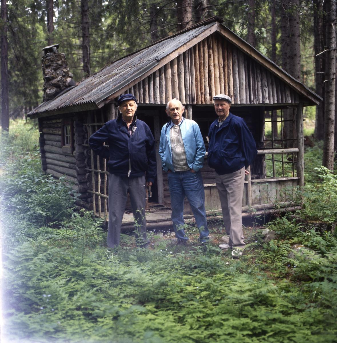 Några män, inklusive bröderna Ahnlund, står framför en gammal timmerstuga i en skogsglänta, 12 juni 1994.