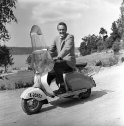 Professor Finn-Erik Vinje på scooter. Ingen øvrige oppl.
