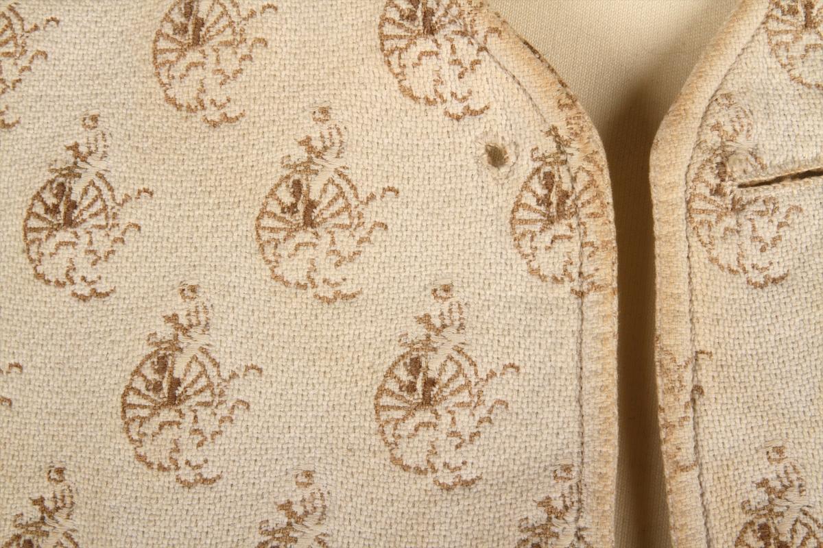 Enkeltknappet vest i lyst, mønstervevet bomullsstoff. , og uten krage. Den har seks håndsydde knapphull og like mange håndsydde småhull til spesialknapper. Samt to stikklommer og én brystlomme. Spensel, men ingen spenne, i ryggen. Vesten har et innvevd motiv som viser velosiped  med mann (Velte-Petter).