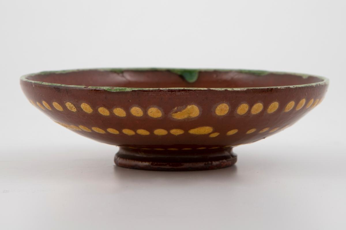 2 kopper med hank og underskåler.  Rødbrunt leirgods med grønnrand rundt munningen. Dekorert med gule prikker og linjer