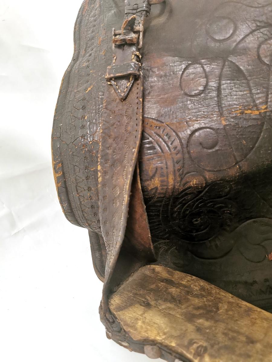 Damesal med bueformet ryggstøtte og fotbrett. Gravert lær, sete kledd med fløyel med brokademønster.
