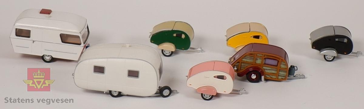 Syv miniatyrmodeller av campere/campingvogner. Fire campere har identisk form, men har forskjellige farger. To campingvogner er laget i plast, mens resterende er laget av metall. Alle sammen har innskriften HONGWELL på undersiden.
