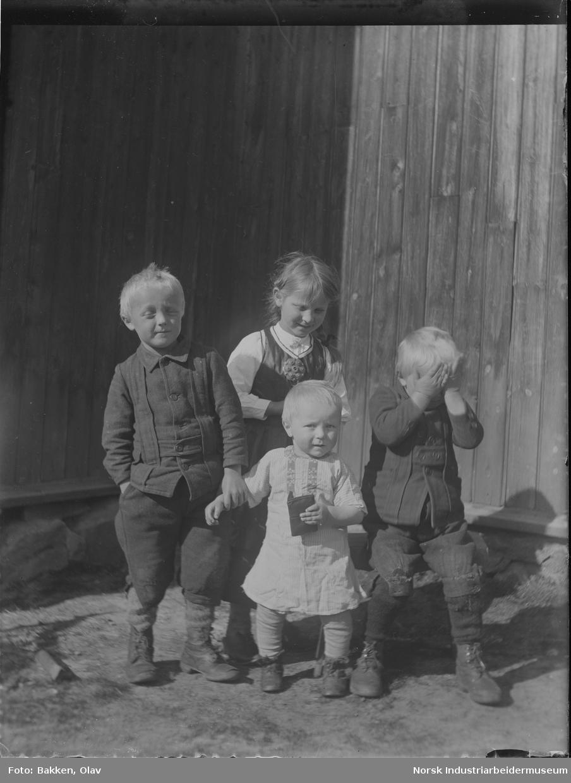 Fire barn stående foran bygg. Ett av barna holder hendene for øynene. Gutt holder mindre barn i armen.