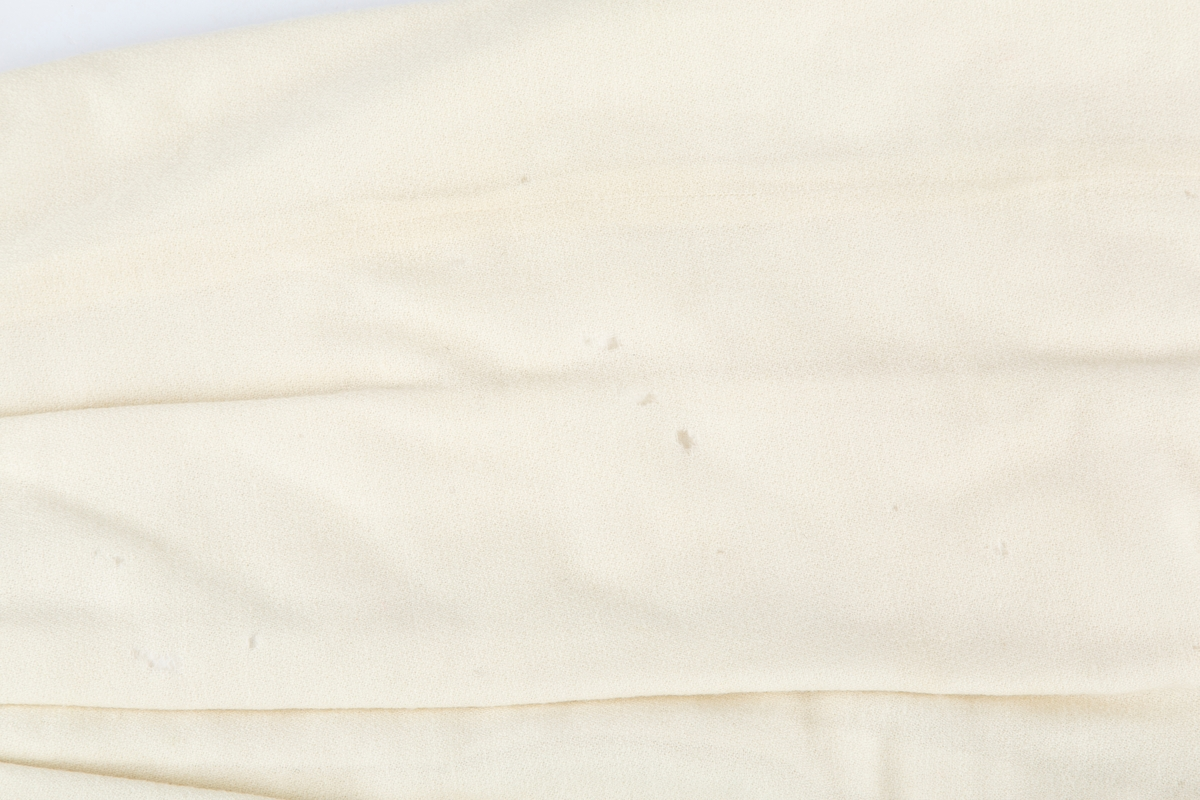 Dåpsdrakt. 2-delt drakt, kjole og kep. Ullmusselin stoff lforet med flanellstoff.  Flere små møllhull på ullstoffet. Tilstand ellers bra. Antakelig hjemmesydd.  A: Kjole.  , bærestykke og skjørt, Åpen  foran, knapping med 2 perlemorknapper og håndsydde knapphull på bærestykke. Lange ermer, små legg ved skulder.  Skjørtet lagt til livet med 2 wienerfoller foran og bak. B: Kep.  Tilnærmet rundklippet. Buet åpning forran. Rysjekant med biser. Krage med stikninger. Lukkes med metallhekte ved kragenHelforet med bomullsflanell