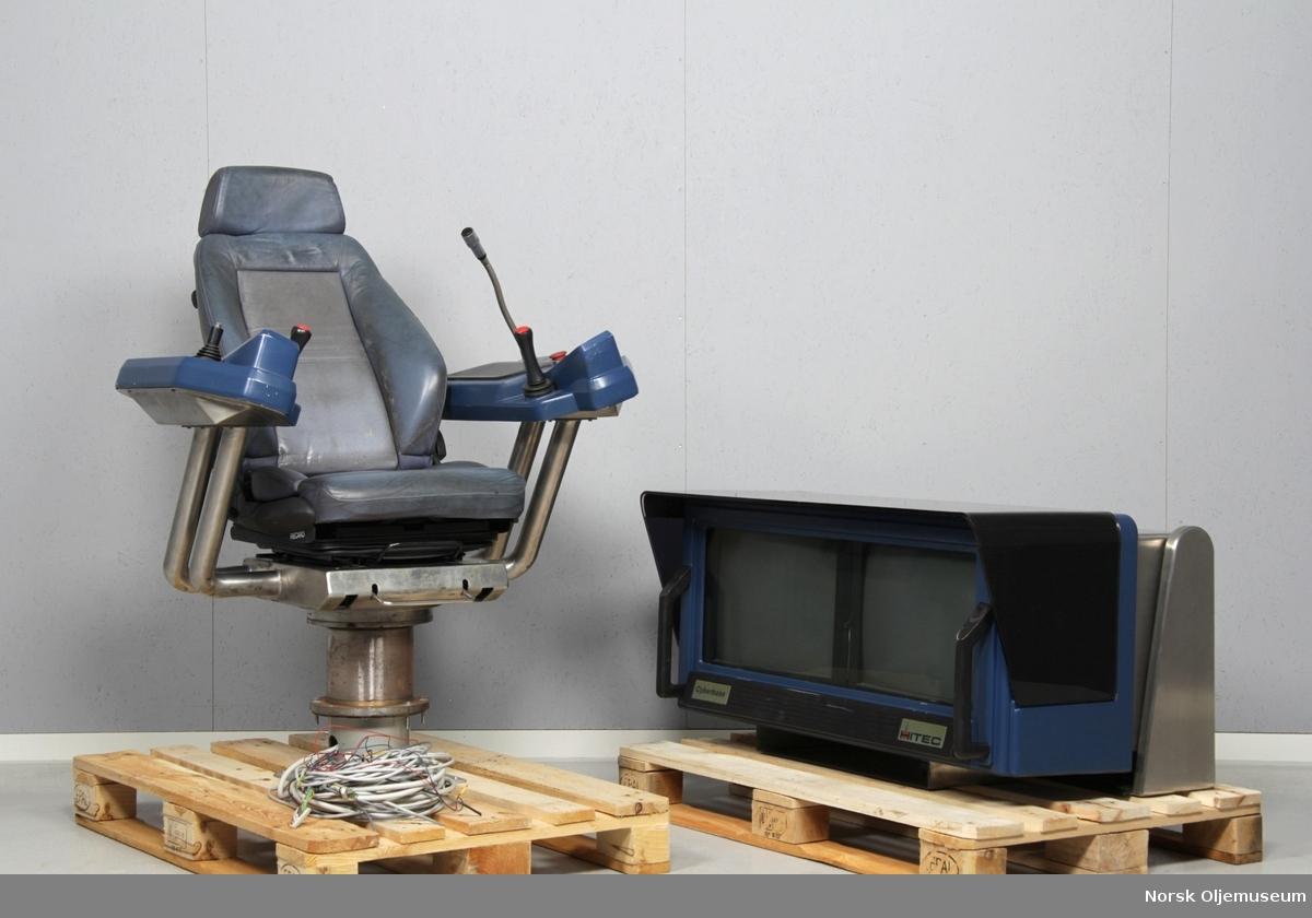 Kontrollutstyr bestående av en operatørstol og et konsoll med dataskjermer.