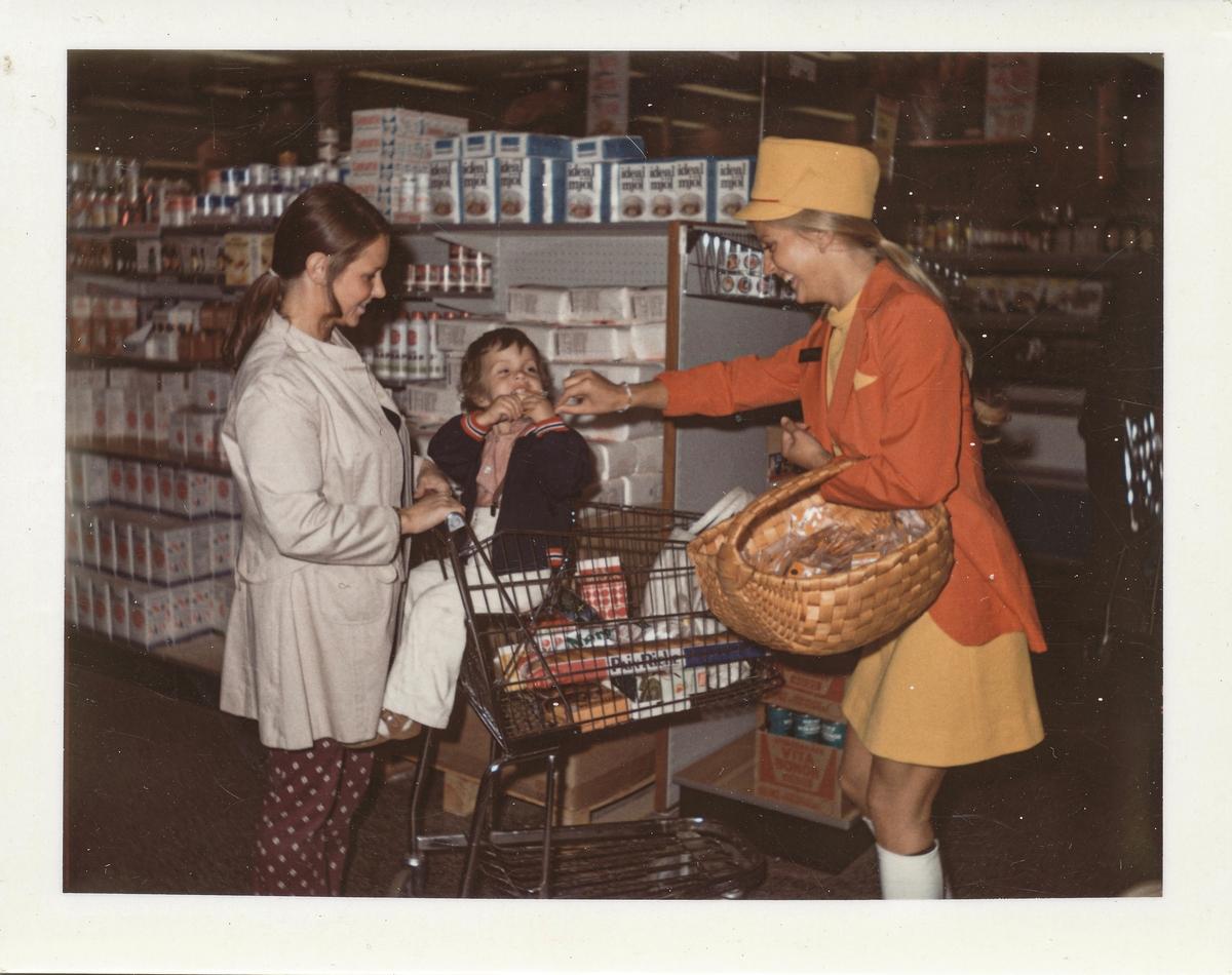 Mataffärssinteriör med kvinna som delar ut smakprover till kunder.