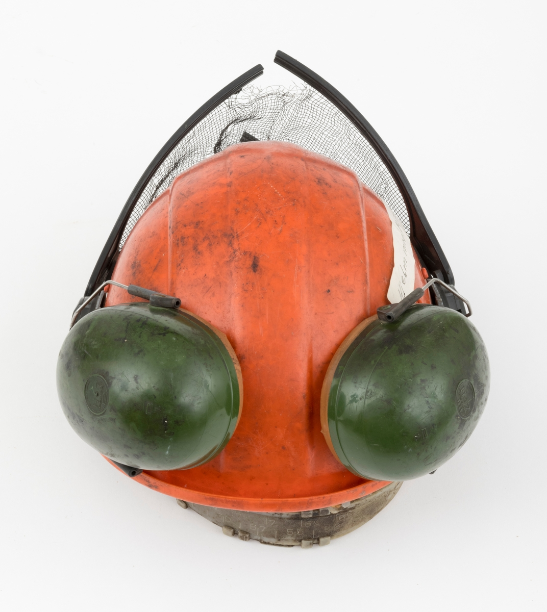 """Hjelm, vernehjelm, hoggerhjelm, skogshjelm, for bruk under skogsarbeid. Hjelmen er støpt i hardplast. Den er utsyrt med visir og hørselvern (øreklokker). Det er en sprekkdannelsen på hjelmens venstre side. Visirets netting og plastramma som visiret er festet til har røket på flere steder. Innvendig er er hjelmen ustyrt med regulerbare plastbånd som kan tilpasses den enkelts hode. Deler av plastbåndet er overtrukket med skinn, svettereim, og i framkant mot panna er det festet skomgummi til plastbåndet. (Det er lær på plastbåndets bakside mot brukerens panne og skomgummi i framkant mot hjemens plastskall.) Den nevnte skomgummien er i ferd med å smuldre opp. Plastbåndet er festet 6 steder i hjelmen. Hjelmen har vridbare klaffer, en på hver side, som kan dekke til eller åpne 2 luftehull. Visir og hørselvern er festet i samme """"plastbrakett"""". Hørselvernene er regulerebare og kan svinges opp på hjelmen med en enkel håndbevegelse. (Hørselvern og visir kan for registrator se ut til å være av noe nyere dato enn selve hjelmen, men det er ikke bekreftet. ) Hørselvernene har for øvrig skomgummpolstring som ligger an mot brukerens ører."""
