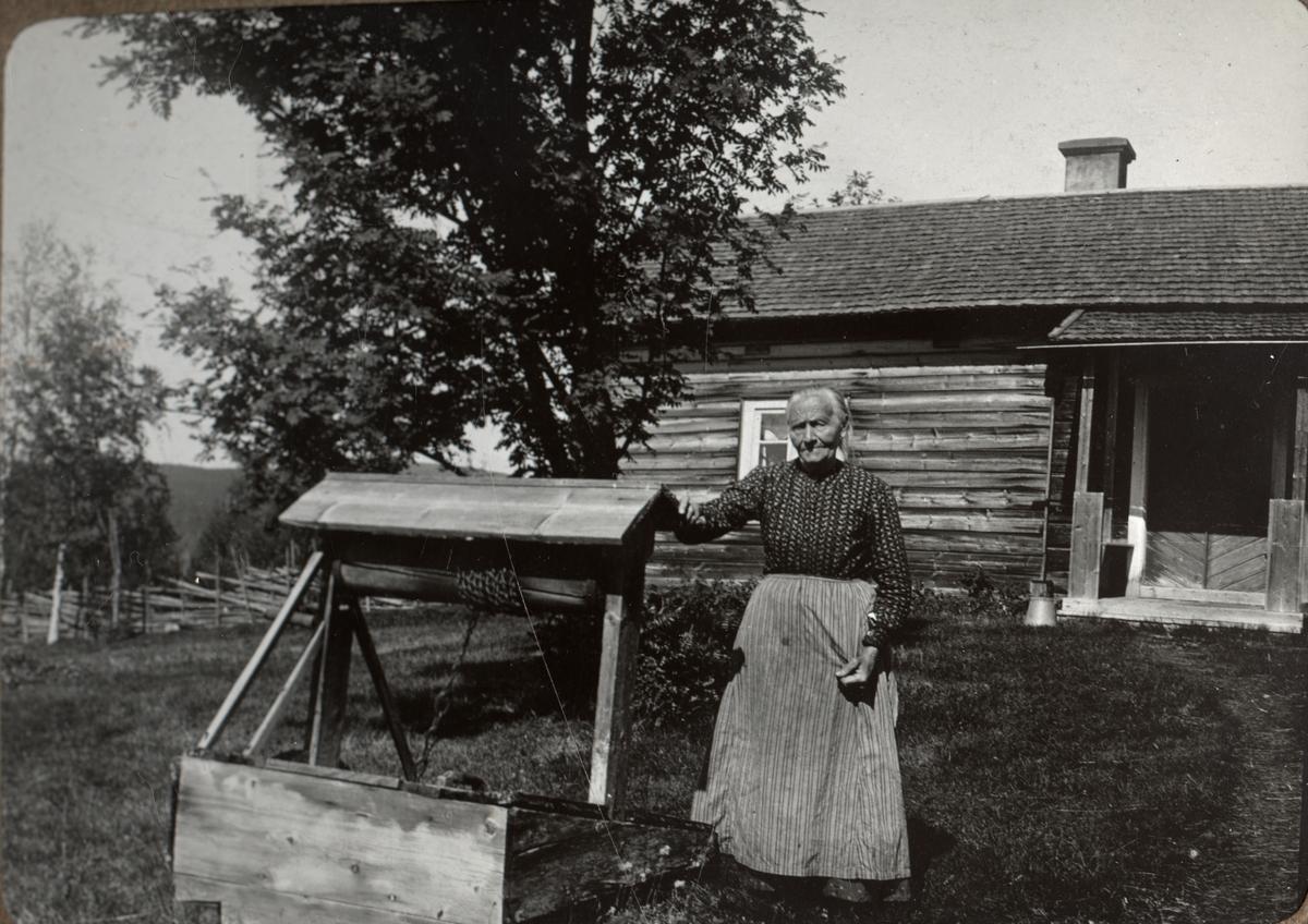 Kvinna vid vattenbrunn. Sommaren 1916. Ur album.