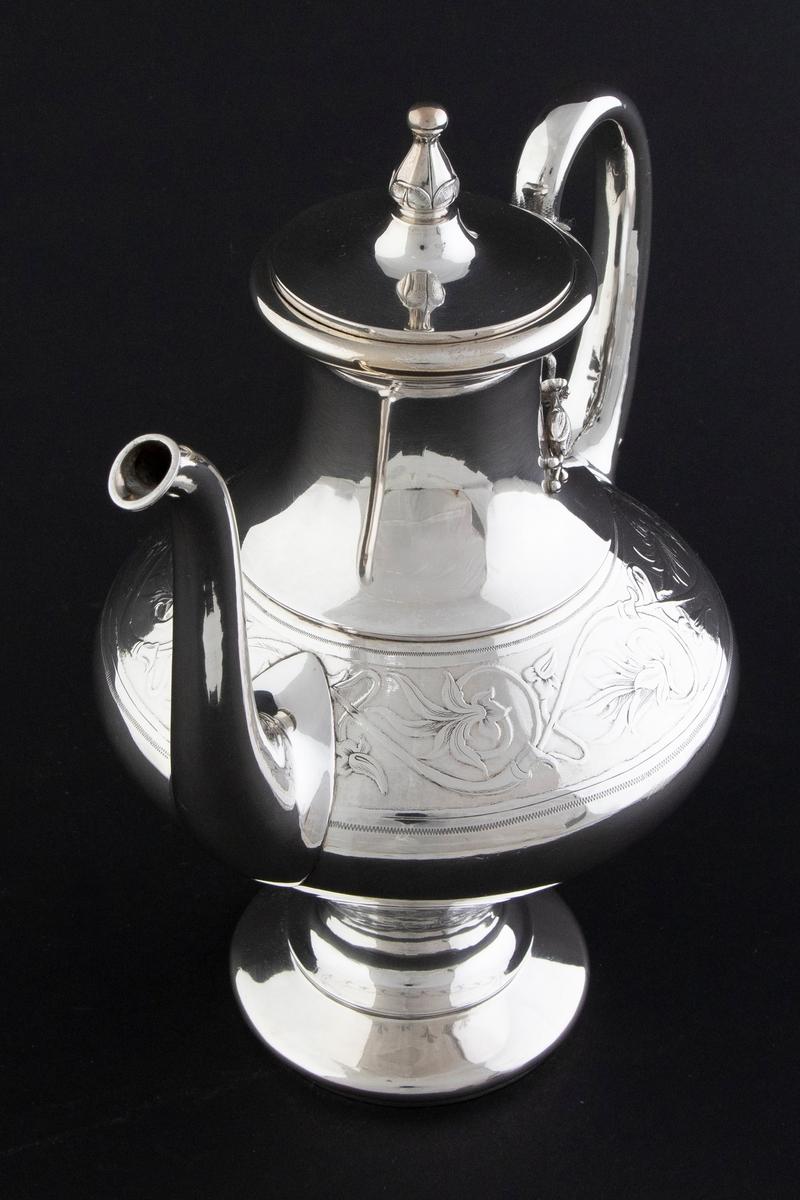 Kaffekanne i sølv. Flattrykket balusterformet korpus med smal hals, som bæres av en sirkulær fot. Korpus er dekorert med en frise av presset rankedekor i lavt relieff. Sirkulært lokk med blomsterformet lokknapp.