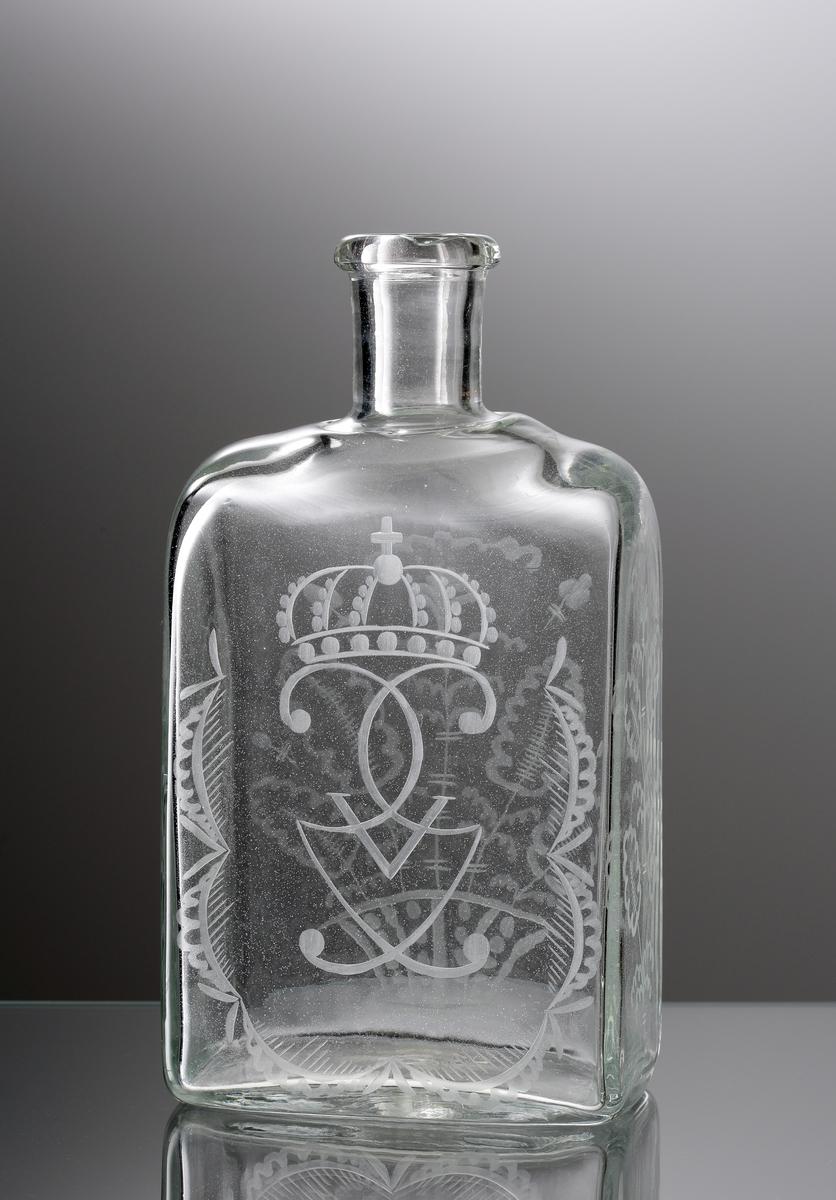 """Brännvinskaraff med rektangulär form. Graverat monogram """"G V"""" under kunglig krona (Gustaf V). Kurbitsdekor runt om och på frånsidan."""