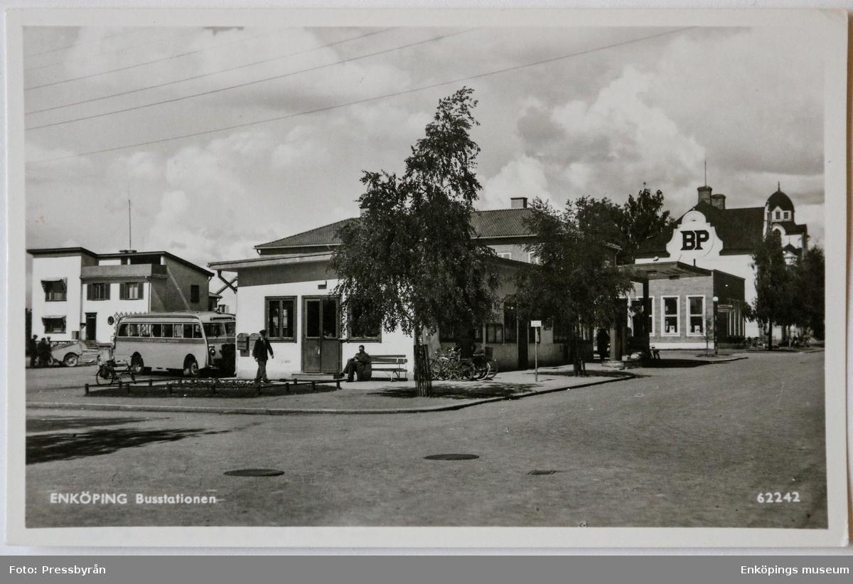 Busstationen Enköping, Gustav Adolf plan. Gustav Adolf plan började iordningsställas 1934 och det byggdes en busstation som togs i bruk 1935. BP-macken som syns i bild flyttades till hörnet Fjärdhundragatan/Westerlundsgatan år 1961. 1967 påbörjas bygget av en ny busstation, som blir klar i juni 1967. I juli 1967 rivs den gamla busstationen och den nya tas i bruk. I den nya busstationen finns kiosk, vänthall, korvkiosk, telefonhytt och Turistinformation. Det blir den nya samlingsplatsen för stadens ungdomar.  Den nya busstationen står där i lite drygt 45år och rivs i januari 2013. Turistinformationen flyttar från Busstationen redan våren 2012, till Enköpings museum på Rådhusgatan 3.     Längs till vänster i bild ser vi tandläkare Hectors villa som uppfördes 1934. Villan är i funkisstil och arkitekt var Gunnar Leche.