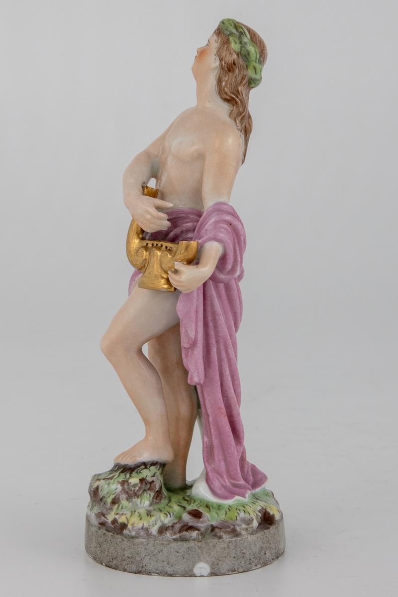 Porselensfigur av mann med forgylt lyre i hånden, som forestiller Apollo. Han står på en sirkulær base i kontrapost. Hvitglasert med polykrom overglasurmaling. Figuren er iført et lilla drapperi, mens kroppen er hudfarget. Han har langt brunt hår og en grønn krans på hodet.