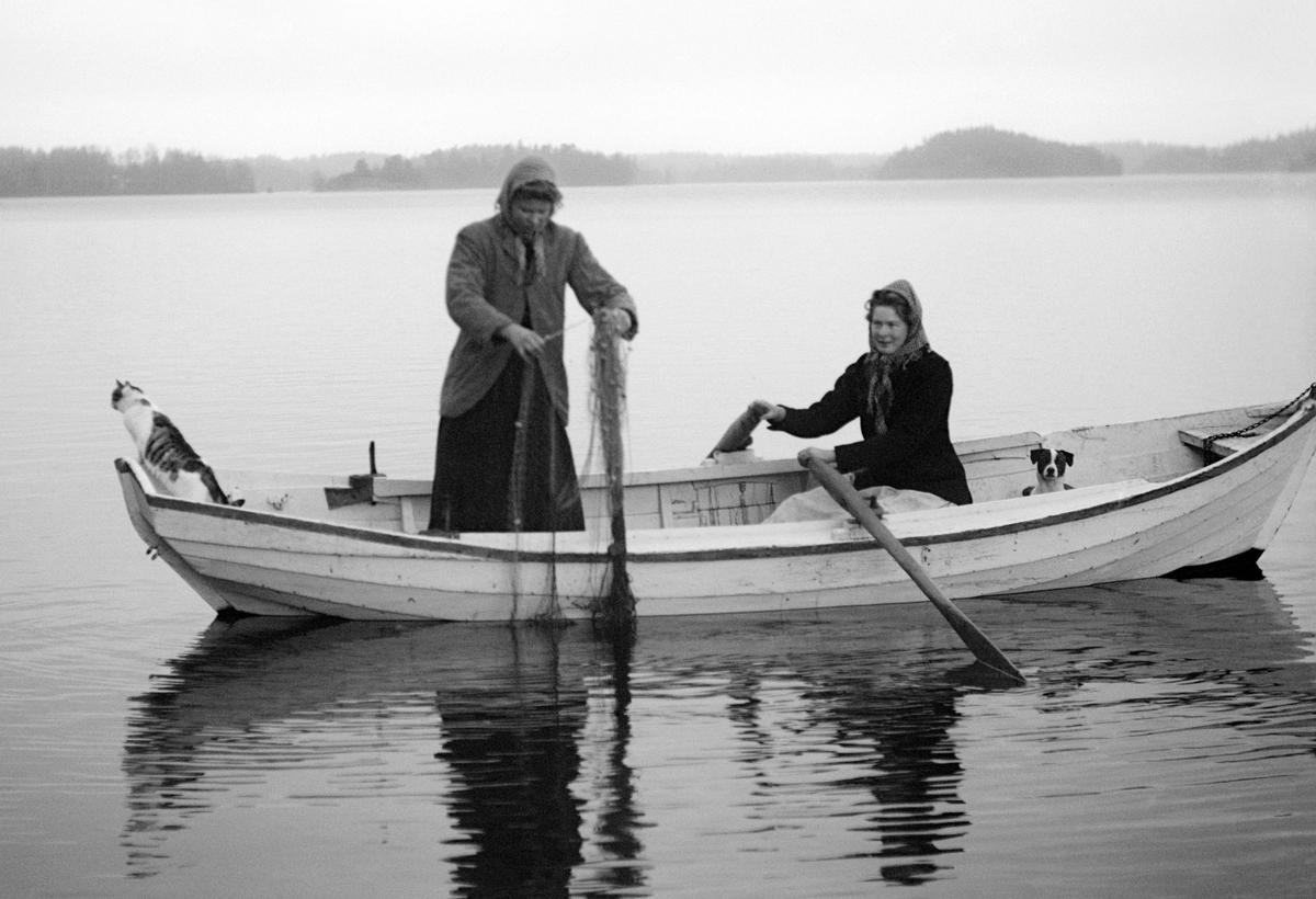Systrarna Ester och Ingeborg Karlsson provar fiskelyckan på Sandfjärden i Sankt Anna. Bygdefotografen Emil Durling förevigade tillfället och han lät av någon anledning sin katt och hund följa med i båten. Ester var under en tid hushållerska hos Emil Durling och är även känd som Ester Bölja Bergström efter taget tillnamn och giftermål.