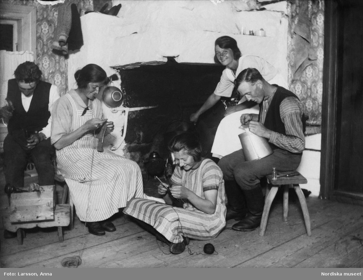 Mosätern. Tre kvinnor, två män handarbetar framför vedspisen