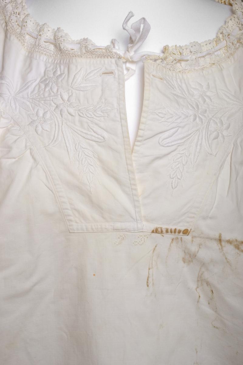 Nattkjolen i tettvevd bomullsstoff med påsydd blonde rundt halsen og armene. Bærestykke i matelassé/quilt. Initialene I (?) H (?) er brodert med hullsøm under bærestykket i front. Finere konfeksjon.