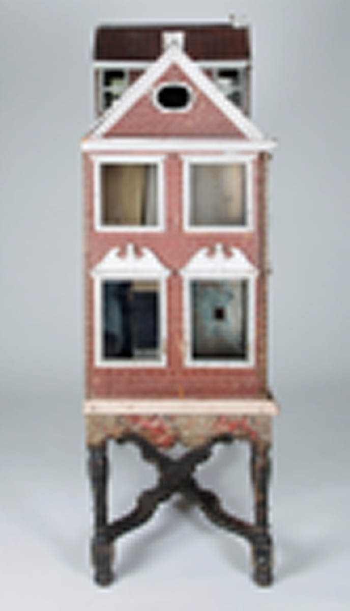 Stort 2-etasjes dukkehus med loftsrom. Tre av sidene er utvendig malt og imiterer mursteinsvegg. Vinduene har hvit innramming, i 1. etasje med bekroning som dannes av en brutt barokkgavl. Det er to rom i hver etasje, på loftet er det et rom. I 1. etasje er det et kjøkken med kamin, tallerkenrekker og en benk. Gulvene er malt med ruter og stjerner i tre rom; to i svart og hvitt og en i svart og rødt. Rommet på loftet har vegger med malt dekor i flere farger på hvit bunn; trær, blomster og fugler. Huset står på et understell med dreide ben som er forbundet med hverandre av flate, buede staver i et x-kryss.  Det er bevart noen gamle møbler: En grønnmalt himmelseng, ni små stoler, en lenestol og en kanapé i bjørk med rokokko-ben og -rygg, en brunmalt klokkekasse og et brunmalt skatoll.