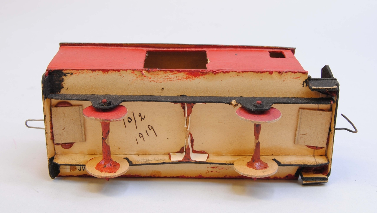 """Röd godsvagn av papp. Delarna är limmade eller sammanfogade med rött lack. Hjulen är gjorda av papp och hjulaxlarna av fyrkantiga träpinnar, troligtvis tändstickor. Vagnskorgen är målad röd med svart underrede och röda hjul. På ena långsidan finns en dörr.  På ena kortsidan finns en öppen plattform med fotsteg samt två fönster och ett fönster på var sida av långsidorna. Taket är lätt välvt och mörkgrått. Under vagnen är datumet """"10/2 1919"""" handskrivet. På kortsidorna av vagnen finns böjd ståltråd, en kork och en ögla för att koppla samman vagnen med andra vagnar eller lok."""