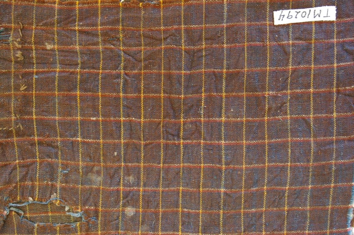Tøyprøve, del av noe. Sist brukt som veggfyll. Tøyet er toskaftsvevd i småruter. Renningen er brun med to gule tråder pr 1 cm brunt. Innslaget er blått i 1 cm ruter, delt opp med 2 tråder gult og 2 tråder orangerødt, vevd sammen til en stripe. Prøva har sårkanter. I ett hjørne en 5x7,5 cm lapp, sydd på med faldesting, brutt hjørne mot tøyprøvens sårkant. I motsatt hjørne en skrått plassert lapp, 15,5x15,5 cm og med jare inn på tøyprøven.
