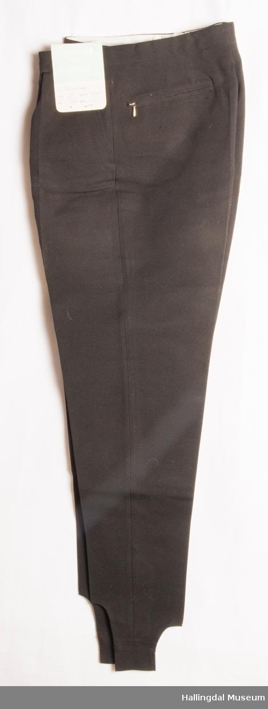 svart strekkbukse i ullstoff, metallglidelås i gylf og metallglidelås i 2 baklommer.  Metallhemper i linningen. 2 framlommer. Bomullslerret i lommene og innvendig for.  Knapper i spensel (inni linningen) til justering av livvidden.