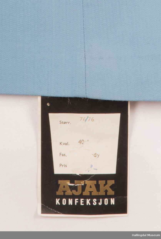 Lys blå bukse i bomull og polyester, slacks. Buksen er kort i livet.  Plastglidelås, 2 metallknapper.