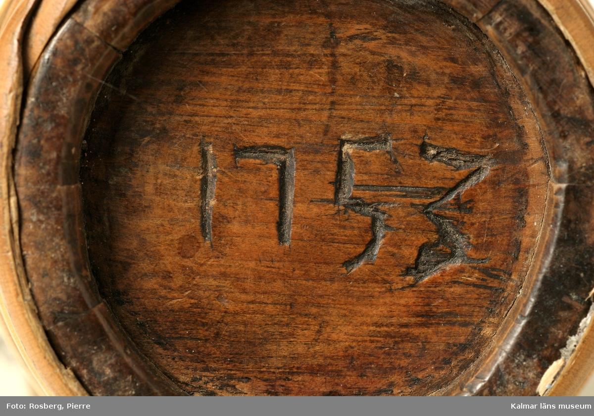 KLM 1750. Brännvinskärl, laggad miniatyrtunna. Laggad med band av vidjor och rotting. I ena gaveln två hål, det ena med isittande trätapp. I andra gaveln inskutet: 1753. Stavarna dekorerade på den synliga delen.