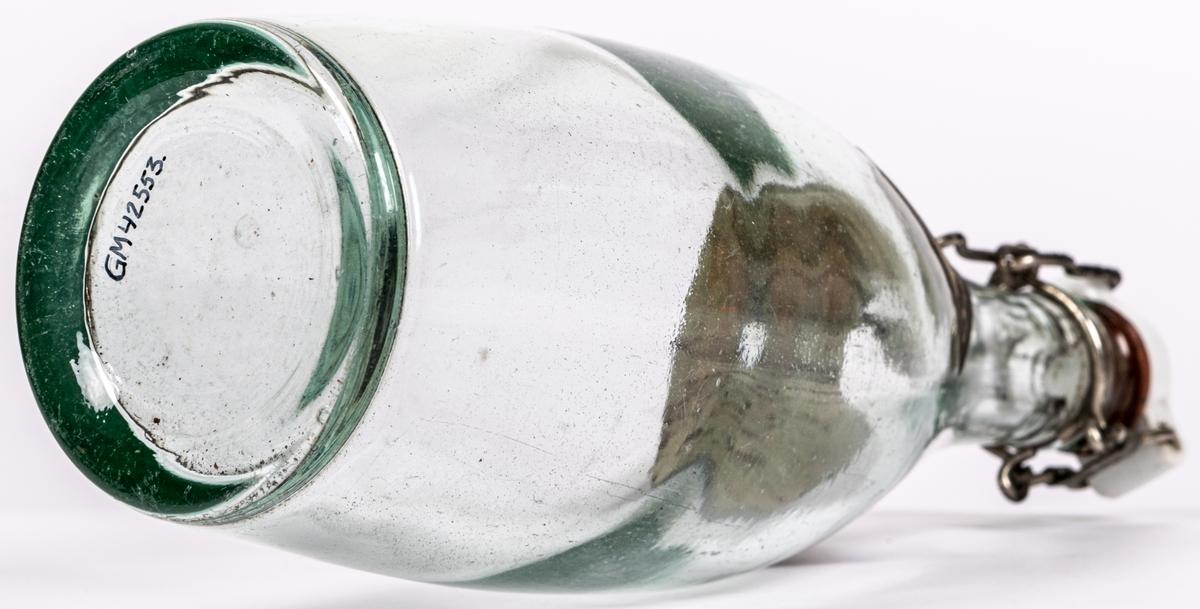 Flaska av genomskinligt glas, bukig form. Patentkort av keramik. Klistrad pappersetikett: Engelskt sodavatten, Mineralvattenfabriken Gevalia, Gefle