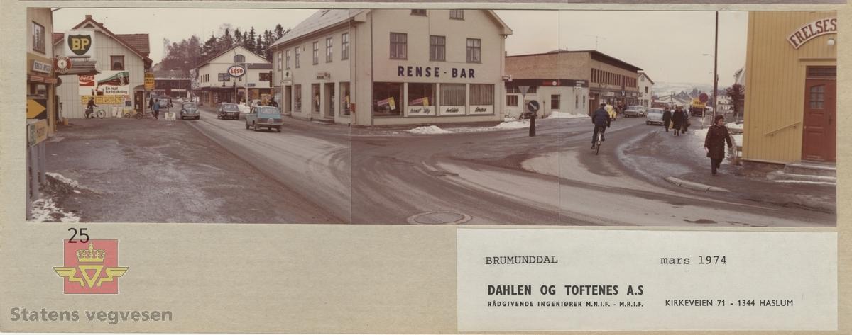 Brumunddal i Ringsaker, Hedmark. Mars 1974.  Sentrum med fotgjengere og syklister på fortau og gate. BP og Esso bensinstasjon.