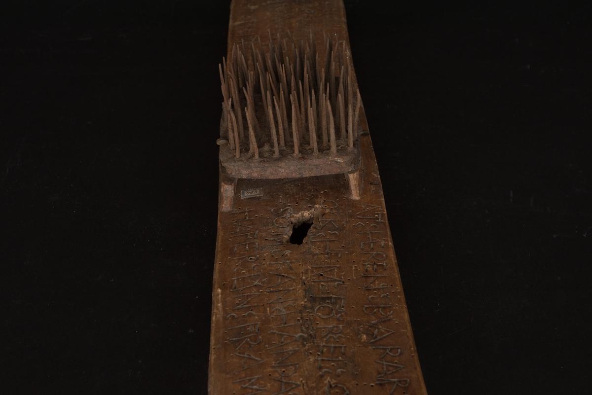 Rektangulär linhäckla av furu.  På mitten finns en upphöjning där en taggförsedd järnplatta är fästad. Brädan är försedd med hål i vardera ände. Brädans ovansida är täckt av en lång inskription med önskan om herrens skydd för eld och brand samt årtalet 1754.  Defekt, ett hål samt gamla spår efter trägnagare över hela träytan.