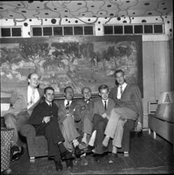 Sex herrar sitter i en soffa. På väggen bakom dem hänger Kar