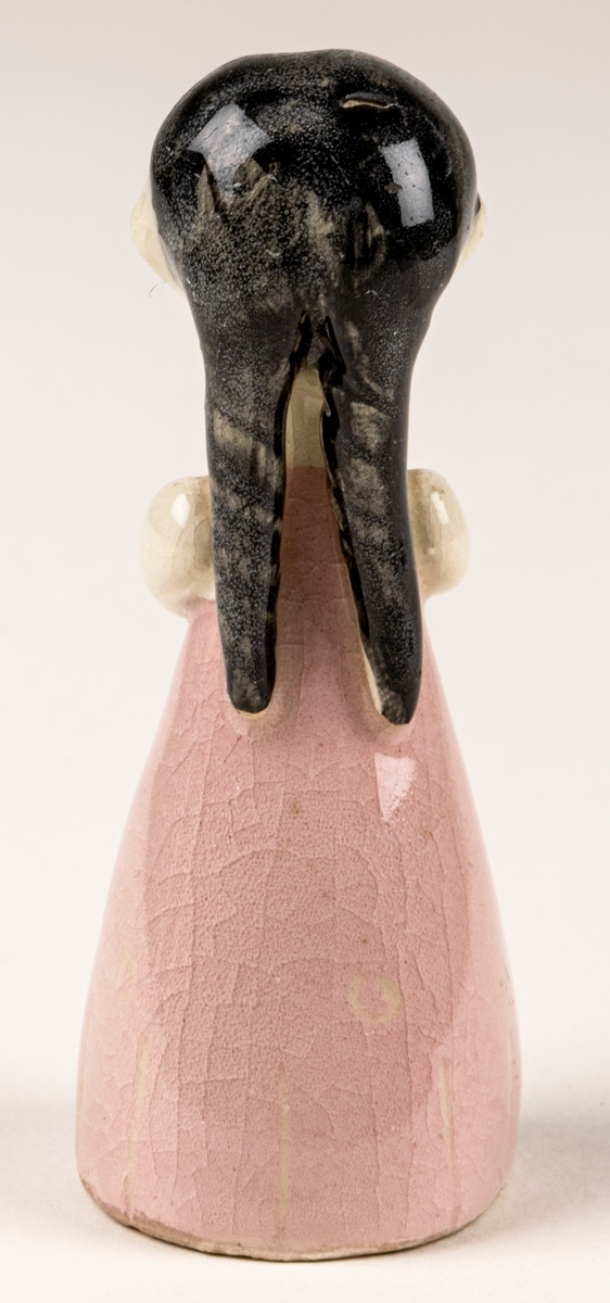 Brudtärna till figuringrupp Brudfölje. Tärnan har mörkt hår och rosa klänning. Formgiven av Dorothy Clough 1955, Gefle Porslinsfabrik. På undersidan svaga rester av stämpeltryckt logga med GEFLE och tre rundugnar.