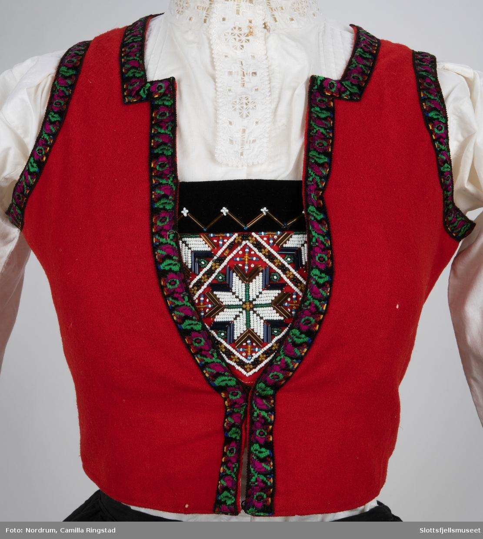 Hardangerbunad for barn. Liv med påsydd bringeklut., skjørt, skjorte og forkle med hardangersøm. Belte og lue.