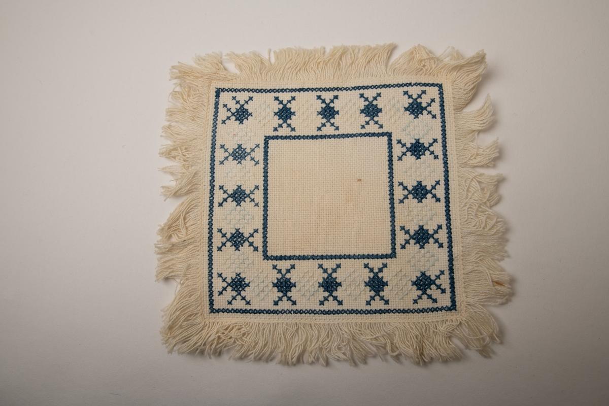 Brikke med korsstingsbroderi. Stramei, blå og hvit bomullstråd. ca. 20,3x20. Firkantet  brikke med lange frynser, langs kanten  en bred bord i Blått med litt hvitt. Tilstand: god.