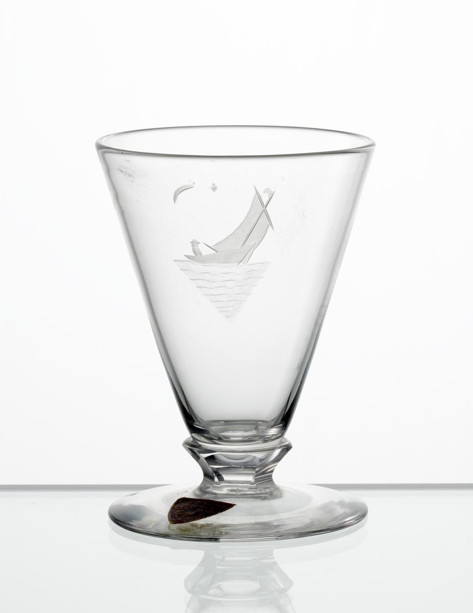 Brännvinsglas, konisk kupa med fasettslipad knapp mellan kupa och fot. Graverad segelbåt med måne i bakgrunden, på kupan. Fabriksmärke: blå botten med guldtext.