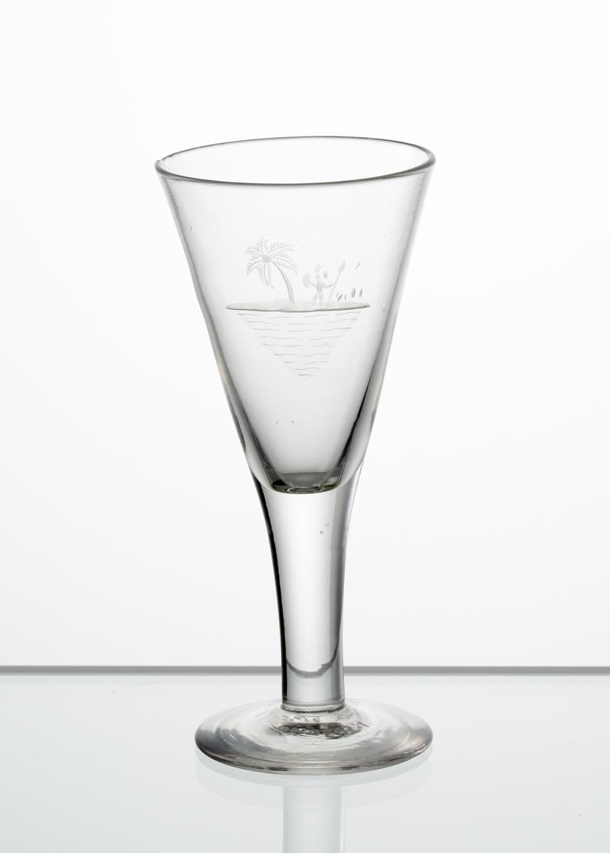 Brännvinsglas, konisk kupa. Graverat söderhavsmotiv bestående av palm och inföding med spjut och sköld på kupan.