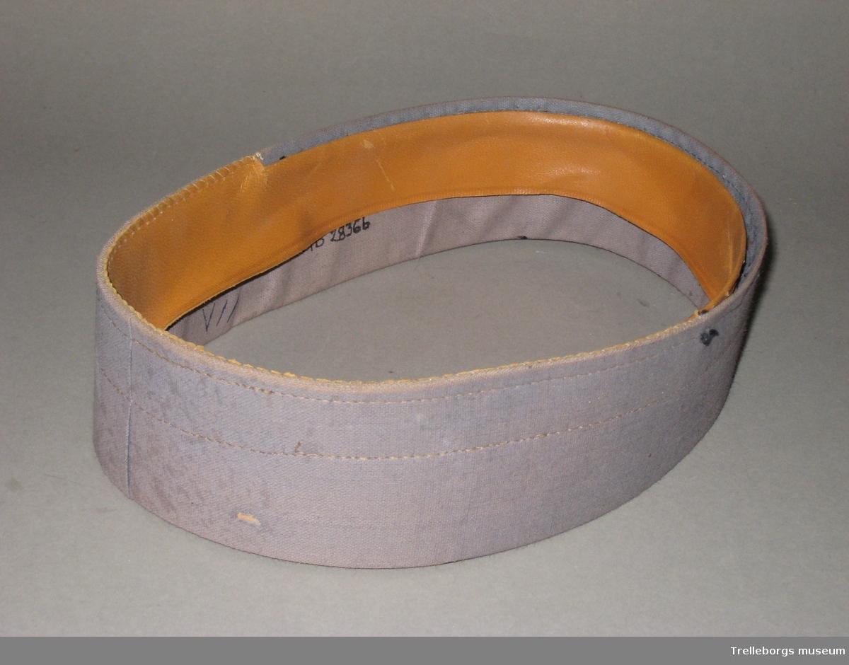 Två stommar till kepsar. a) Pappstome klädd i grå textil. b)Pappstomme klädd i grå textil. Klädd med skinnband på insidan.