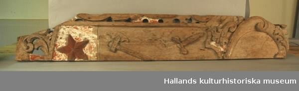 Vänstra delen av ett epitafium. Med utskärningar, bl.a. stjärna, yxa och hammare.  Överst kartusch. Rester av kredering samt röd och grön lim (?) färg. 1700-tal.