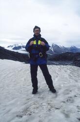 En man med mindre ryggsäck står på ett snöklätt berg, Dronni