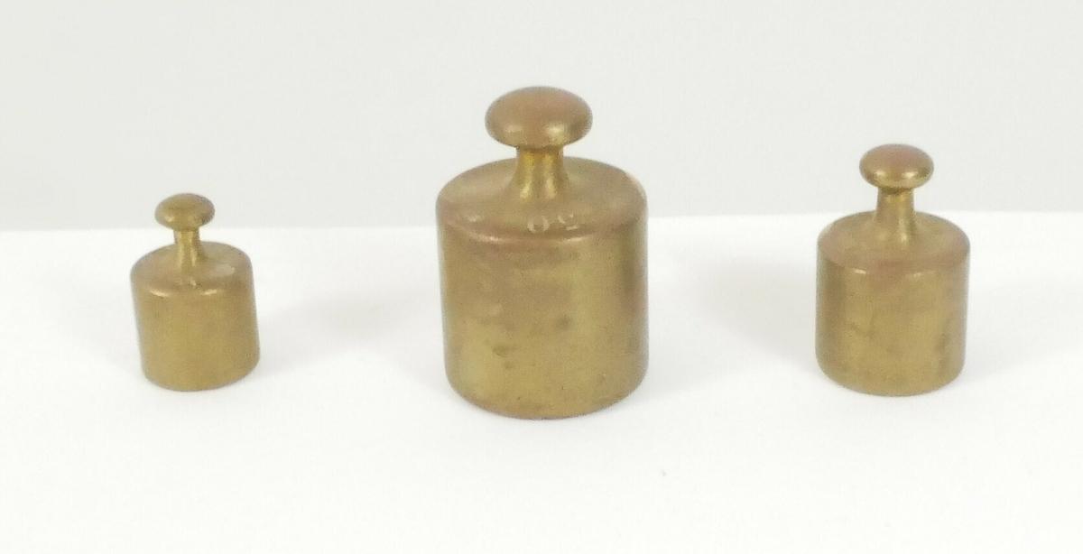 Vekten er demontert og består av flere elementer: To runde skåler.  To metallstenger med en rund del nederst til å feste skålene på.  En rektangulær metalldel  Til vekten tilhører tre små lodd i ulike størrelser.