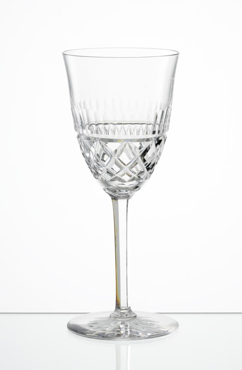 Vitvinsglas med lätt klockformad kupa, skärslipad nedre del med olivslipad bård. Fasettslipat högt ben. Fot med skärslipad stjärna i botten.