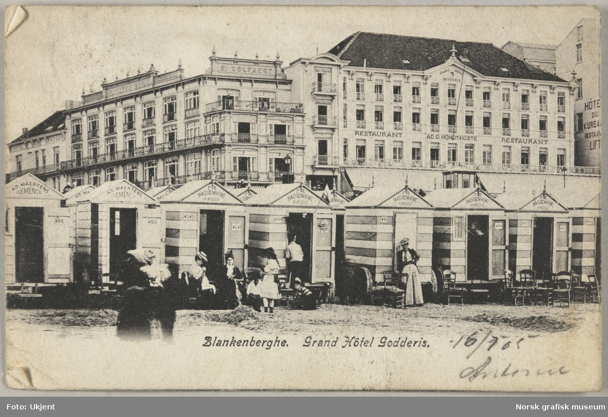 """Postkort fra Antonie til Olava Lunde. Bildet er fra stranda i Blankenberge, Belgia, med """"Grand Hôtel Godderis"""" i bakgrunnen."""