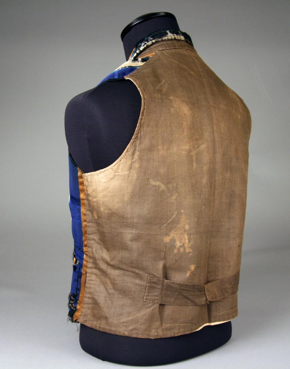 Brudggumsväst av randigt siden i blått, gult och svart, smal nedvikt krage, två fickor fram, dubbel knäppning. Ryggstycke av grått kyprat tyg, foder av vit linnlärft.